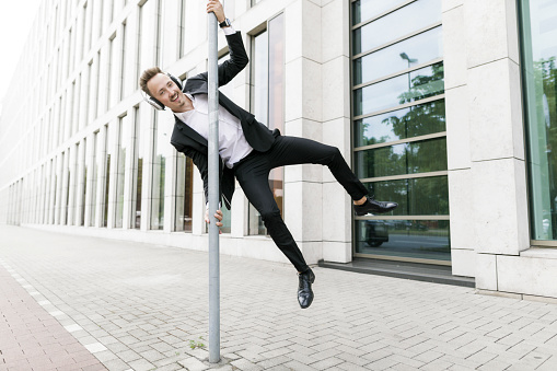 Happy young businessman wearing headphones jumping at lamp post in the city - gettyimageskorea