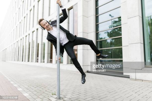 Happy young businessman wearing headphones jumping at lamp post in the city