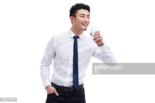 Happy young businessman with milk
