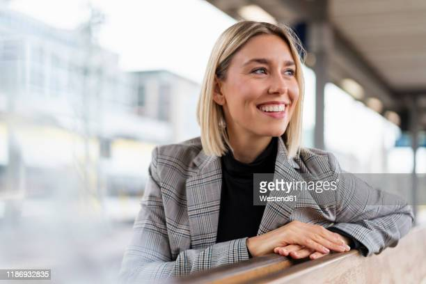 happy young businesswoman at the train station looking around - bahnhof stock-fotos und bilder