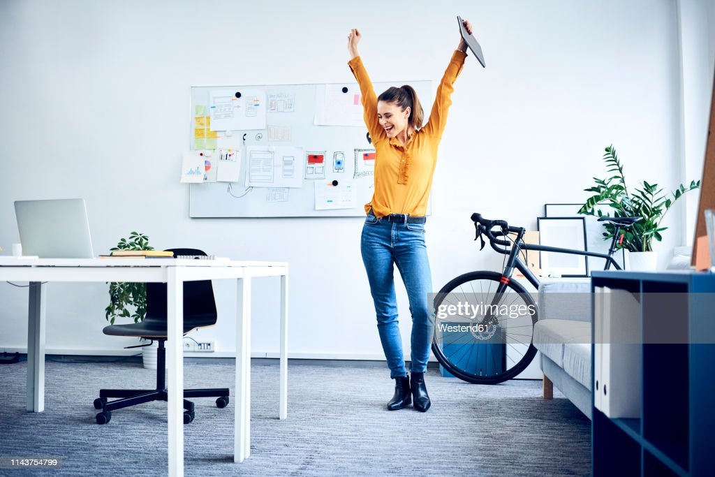 Happy young businesswoman cheering in office : Stock Photo