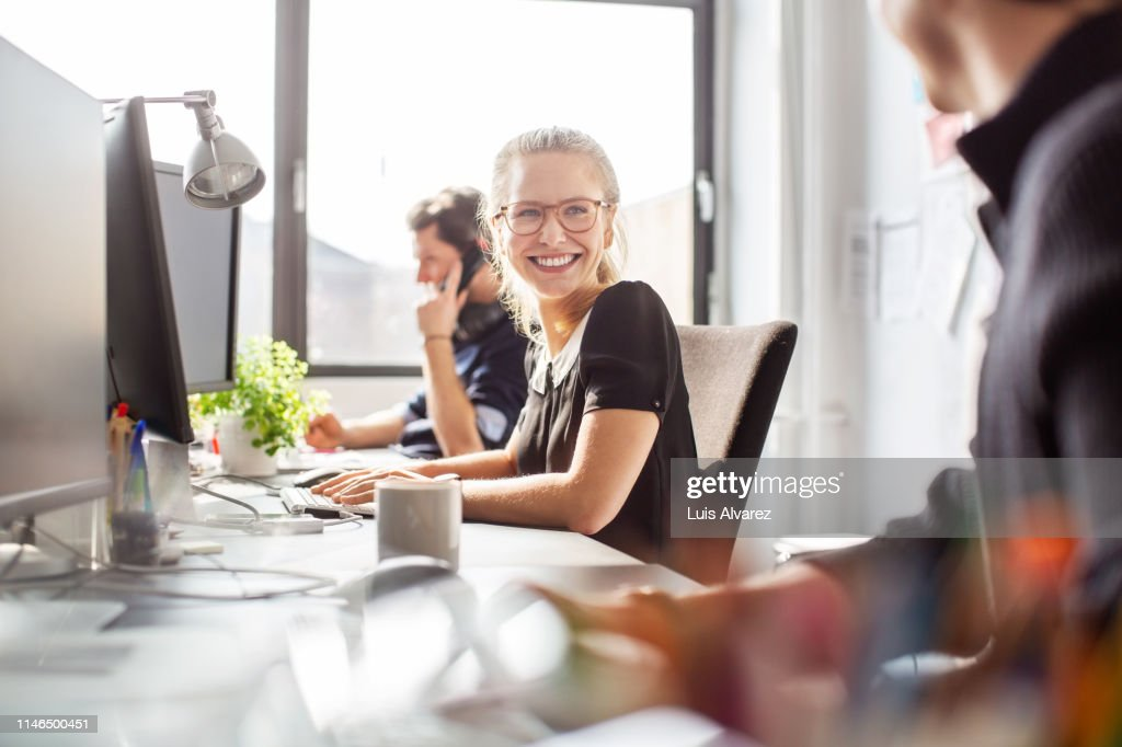 Happy young businesswoman coworking with her team : Stock-Foto