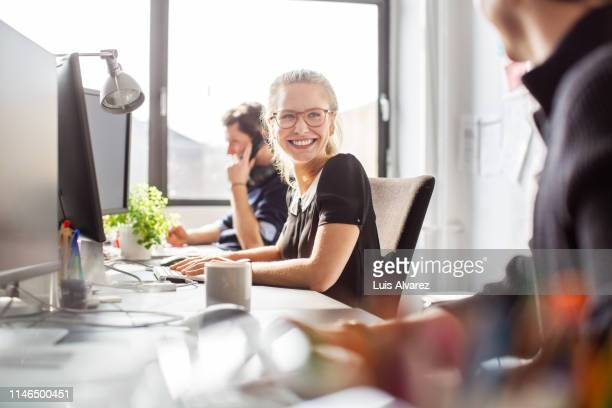 happy young businesswoman coworking with her team - arbeitsstätten stock-fotos und bilder