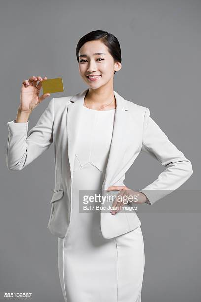 Happy young businesswoman holding a credit card