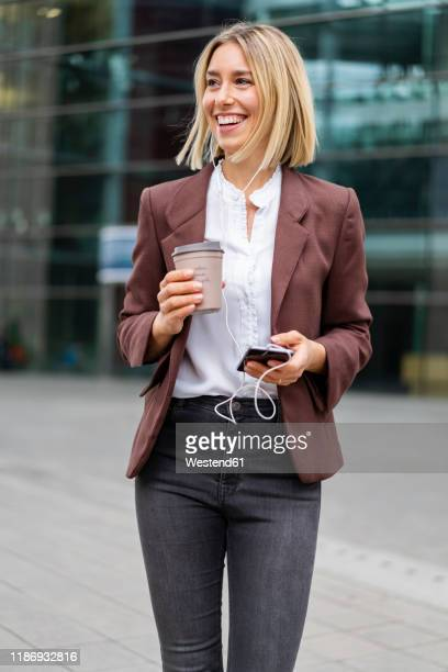 happy young businesswoman in the city on the go - pant suit stock pictures, royalty-free photos & images