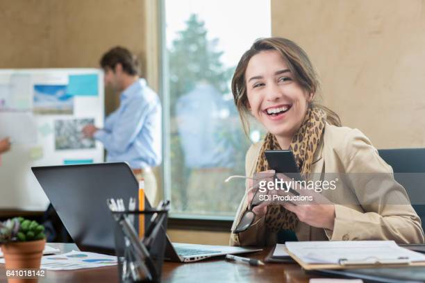 Happy young businesswoman smiles while working