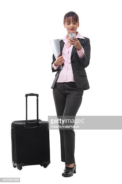 Happy young businesswoman with luggage reading text message
