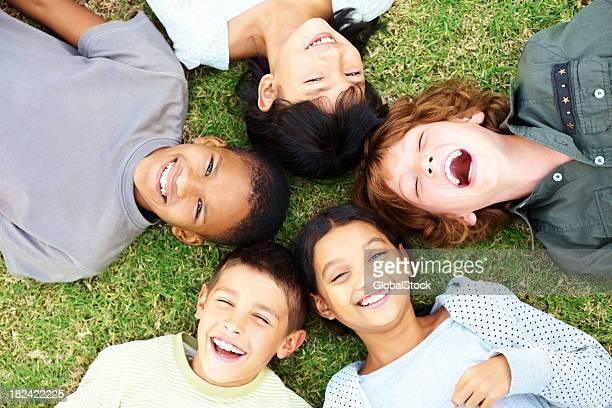 Glückliche Kleine Kinder auf Gras liegen und Lachen