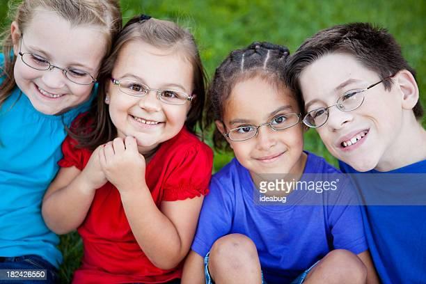 Glückliche kleine Kinder mit Brille lächelnd im Freien