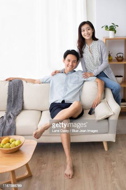 happy young chinese couple using smartphone in living room - 足を組む ストックフォトと画像
