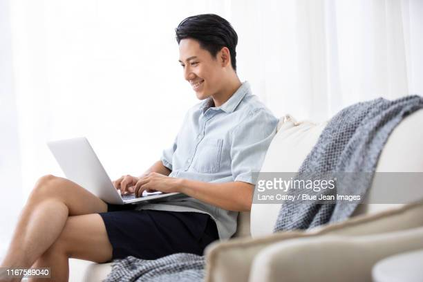 happy young chinese man using laptop in living room - 歯を見せて笑う ストックフォトと画像