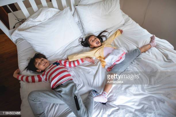 happy young chinese sister and brother playing on guest bed - free images stock pictures, royalty-free photos & images