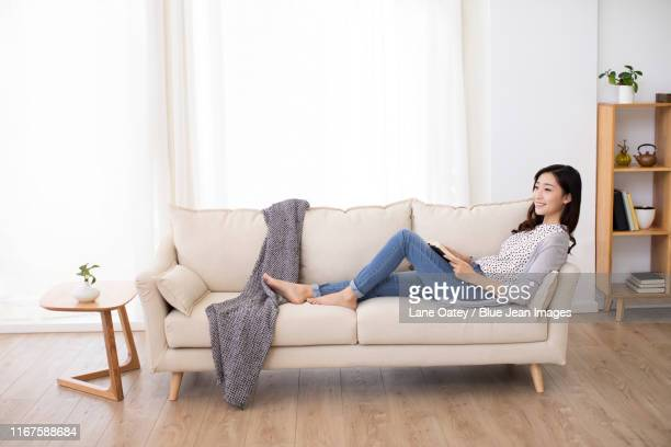 happy young chinese woman reading book on sofa - 寝具 ストックフォトと画像