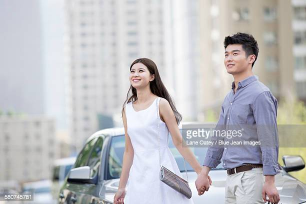 Happy young couple and car