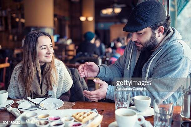 Happy Young Couple Chatting in a Restaurant Cafe