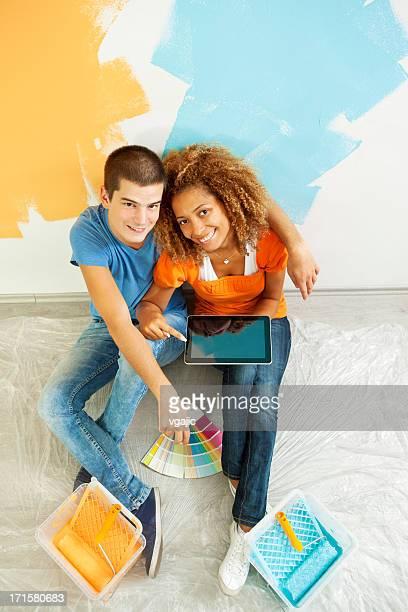 feliz jovem casal escolher cor de tinta para sua casa - tintura - fotografias e filmes do acervo