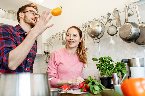 Happy young couple cooking together in kitchen - gettyimageskorea