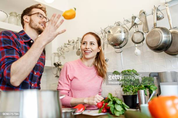 happy young couple cooking together in kitchen - freshness stock-fotos und bilder
