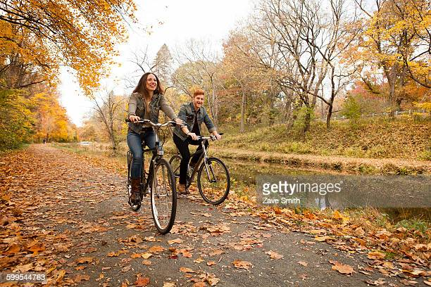 happy young couple cycling along riverside in autumn - riverbank stock photos and pictures