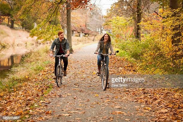 happy young couple cycling on riverside in autumn - riverbank stock photos and pictures