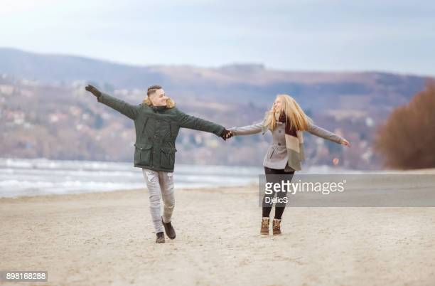 Happy young couple dancing on a cold winter day.