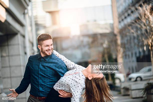 Happy Young Couple Dancing on City Street at Sunset