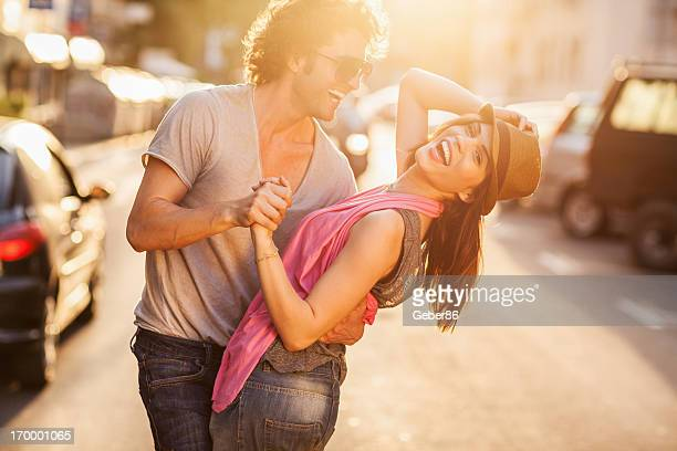 Happy young couple dancing on the street