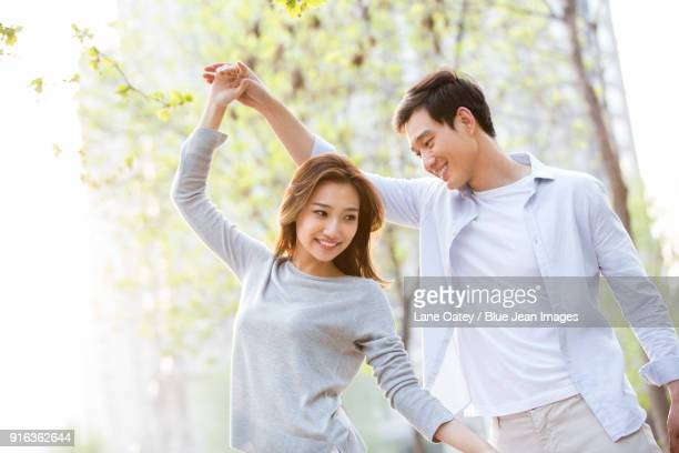 Happy young couple dancing outdoors
