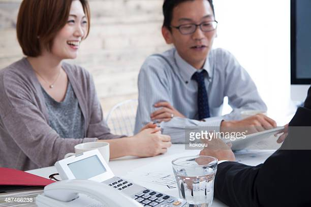 happy young couple discussing with consultant in office - real estate office stock photos and pictures