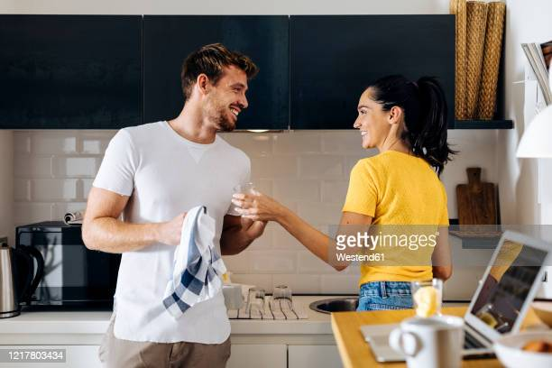 happy young couple doing the dishes in the kitchen at home together - 皿洗い ストックフォトと画像