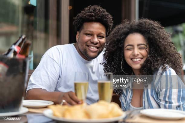casal jovem feliz bebendo cerveja em um bar - retrato - colorido pastel - fotografias e filmes do acervo