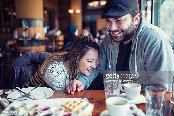 Happy Young Couple Drinking Coffee and Laughing in Cafe