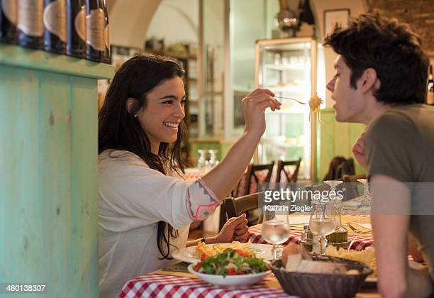 happy young couple eating together in restaurant - daten stockfoto's en -beelden