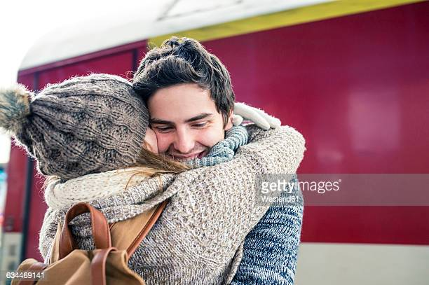 Happy young couple embracing in front of train