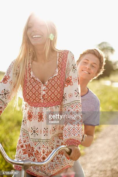 Happy young couple enjoying bicycle ride at countryside