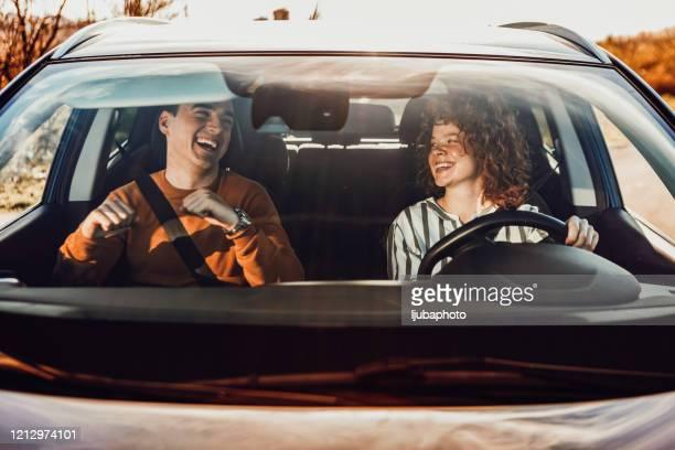 felice giovane coppia godendo in auto - punto di vista frontale foto e immagini stock