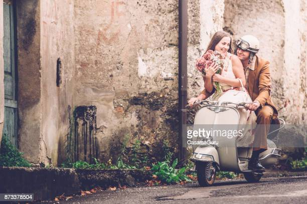 happy young couple enjoying on vintage vespa motorcyle - moped stock photos and pictures