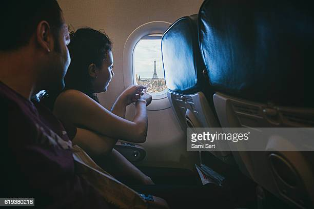 Happy young couple enjoying Paris from the airplane window