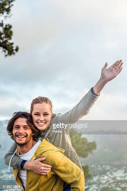 Glückliches junges Paar genießen Huckepack nehmen Sie im Freien
