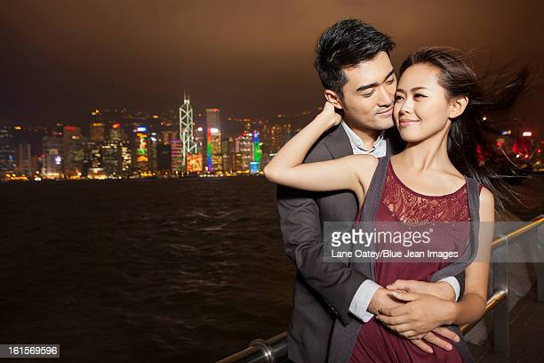 Happy young couple enjoying the night view of Victoria Harbor, Hong Kong