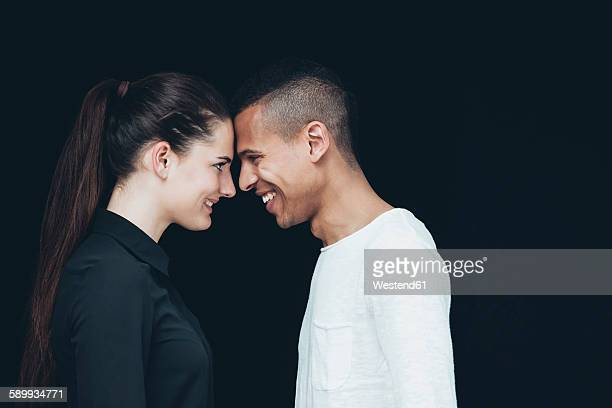 Happy young couple face to face in front of black background