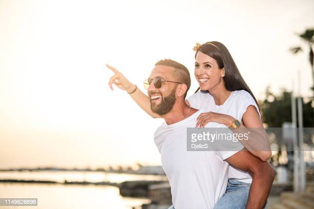 happy young couple falling in love on sunset on cyprus island. - love island stock pictures, royalty-free photos & images