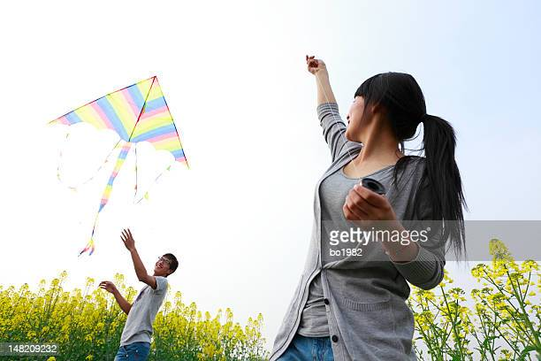 happy young couple flying kite