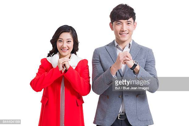 happy young couple greeting for chinese new year - オープンネック ストックフォトと画像
