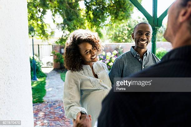 Happy young couple greeting man during visit