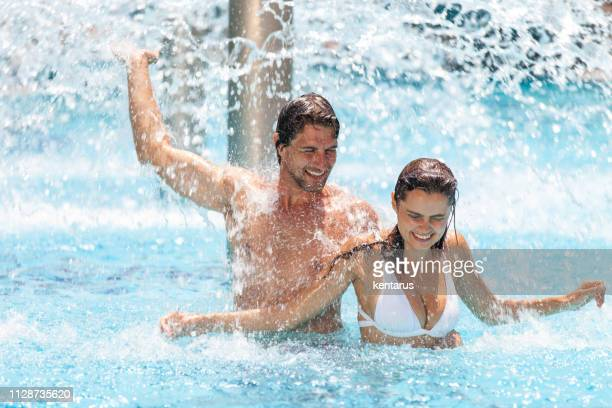 Happy young couple having fun in pool under splashing water fountain during holiday