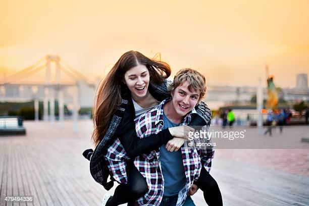 Happy young couple having fun on piggy back, Tokyo.