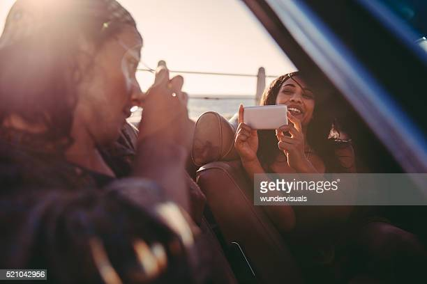 Happy young couple having fun with pictures in convertible