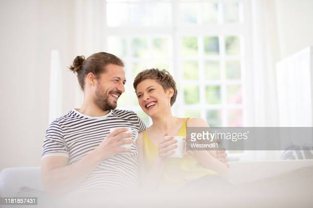 happy young couple holding cups on couch at home - convenience stock pictures, royalty-free photos & images