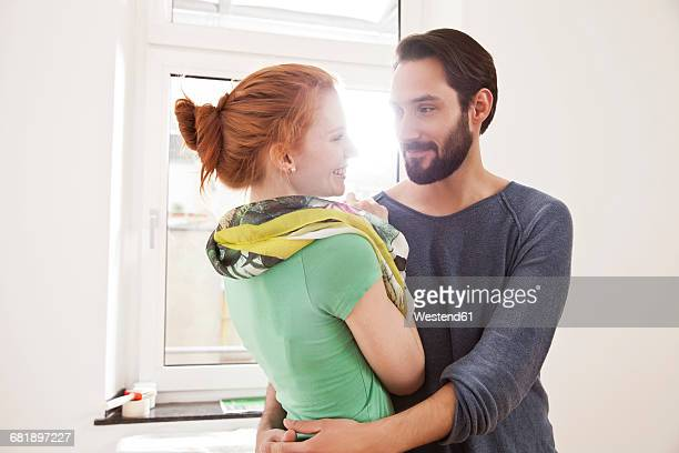 Happy young couple hugging in white room